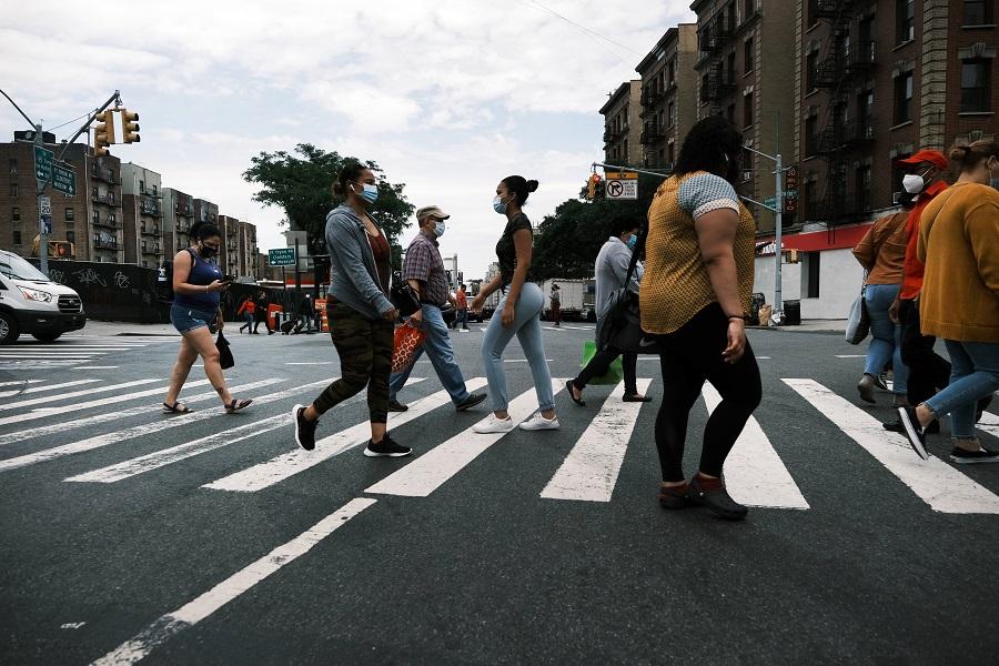 People walk through the Washington Heights neighborhood in Manhattan on 11 June 2021 in New York City, US. (Spencer Platt/Getty Images/AFP)