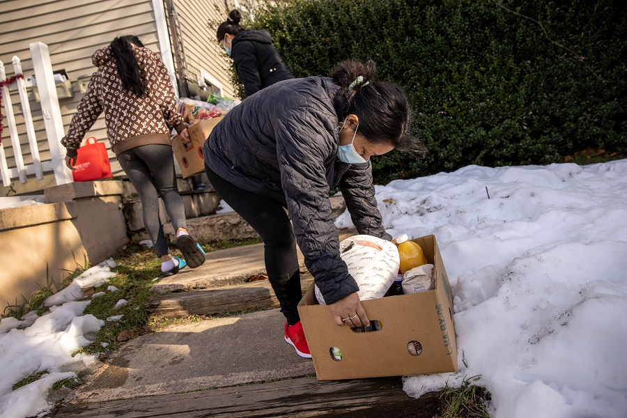 A family with Covid-19 carries free groceries inside which had been delivered by the non-profit Family Centers on 22 December 2020 in Stamford, Connecticut, US. (John Moore/Getty Images/AFP)