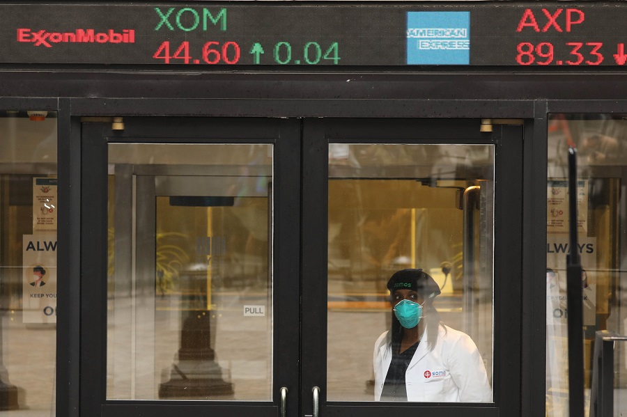 A medical worker stands at the entrance to the New York Stock Exchange on the first day that traders are allowed back onto the historic floor of the exchange on 26 May 2020 in New York City. (Spencer Platt/Getty Images/AFP)