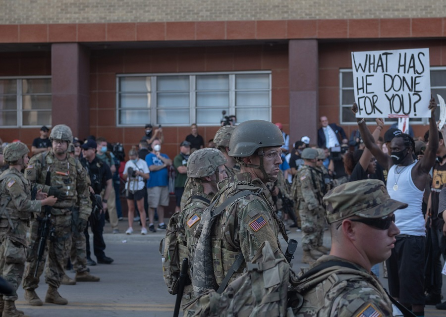 Members of the National Guard stand in formation as protesters march and protest near the BOK Center in Tulsa, Oklahoma on 20 June 2020. (Seth Herald/AFP)