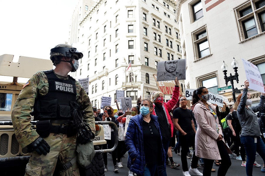 "A National Guard soldier looks on as people march from Boston City Hall to just outside the Boston Police Station to call for Police Department reform as part of the ""Unite Against Racist Police Terror! Boston Speakout and March"" in Boston, Massachusetts on 7 June 2020. (Joseph Prezioso/AFP)"
