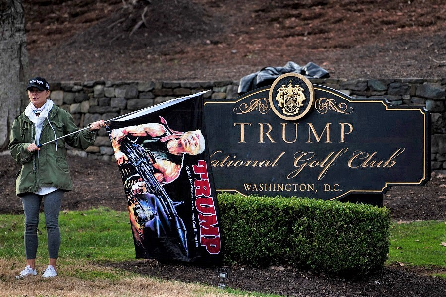 A supporter of US President Donald Trump waits outside the Trump National Golf Club as the president plays golf, 13 December 2020, in Sterling, Virginia. (Brendan Smialowski/AFP)