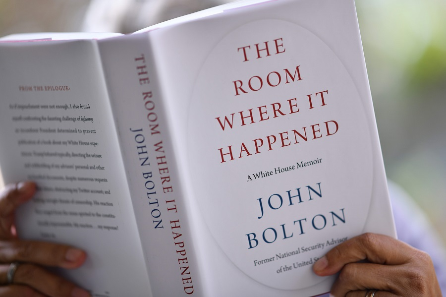 "This illustration photo taken on 23 June 2020 shows a woman reading John Bolton's book ""The Room Where it Happened"" on the day of its release in Los Angeles. (Chris Delmas/AFP)"
