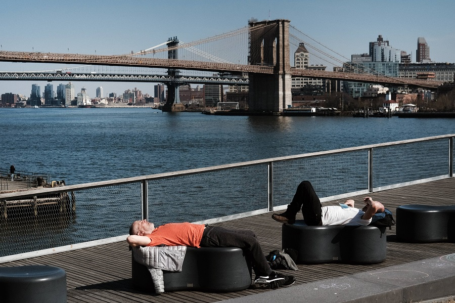 People relax in the sun in Manhattan on a warm afternoon on 9 March 2021 in New York City. (Spencer Platt/Getty Images/AFP)