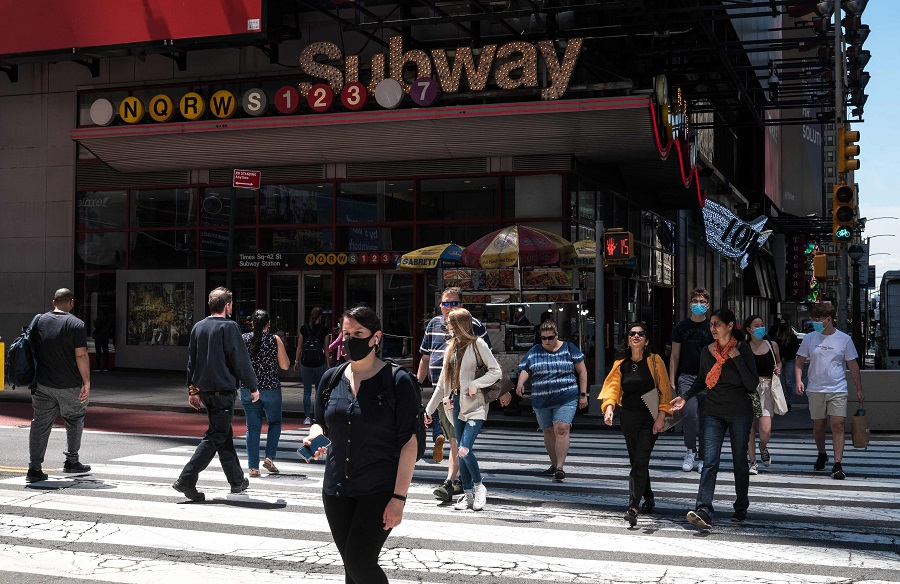 People walk past a subway stop sign on 17 May 2021 in New York City, US. (Angela Weiss/AFP)