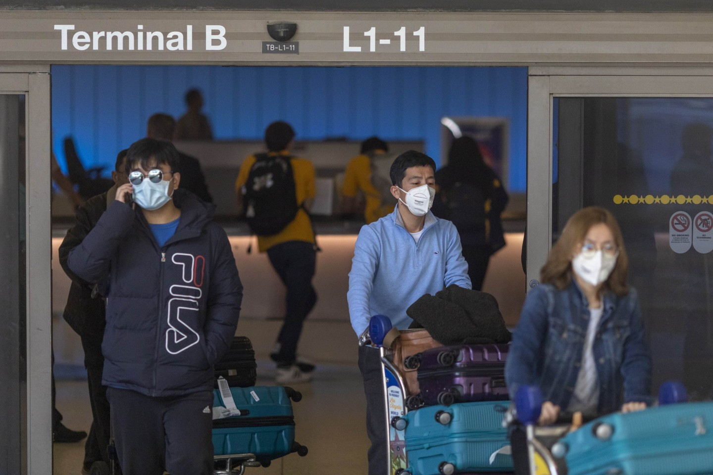 In this photo taken on 2 February 2020, travelers arrive at LAX Tom Bradley International Terminal wearing medical masks for protection against the coronavirus outbreak. Foreign nationals who have been in China in the last two weeks and are not immediate family members of US citizens or permanent residents will be barred from entering the US. (David McNew/Getty Images/AFP)