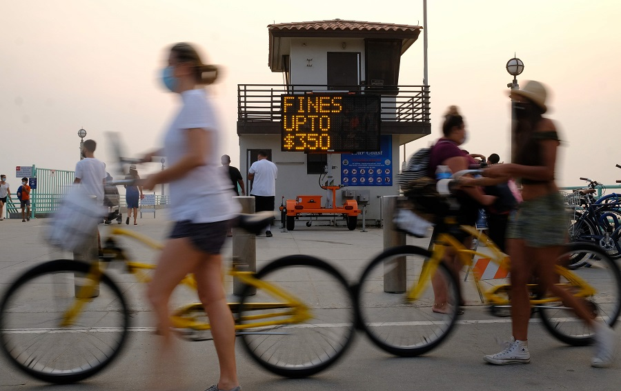A sign reminding people the fine for not wearing a mask can be as much as $350 is seen by the pier on 7 September 2020 in Manhattan Beach, California, amid the coronavirus pandemic. (Chris Delmas/AFP)