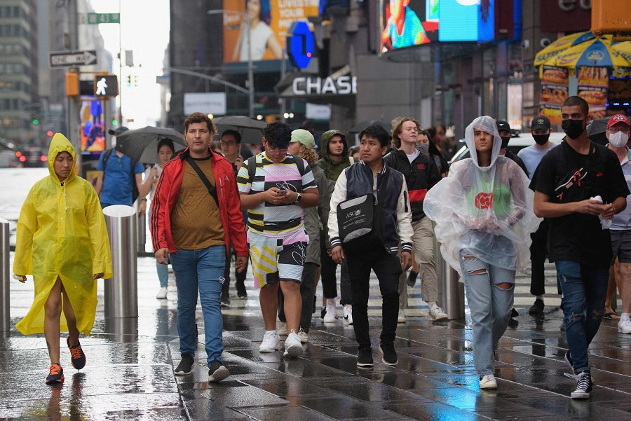 People walk through Times Square during rainfall in New York City, US on 23 August 2021. (Angela Weiss/AFP)