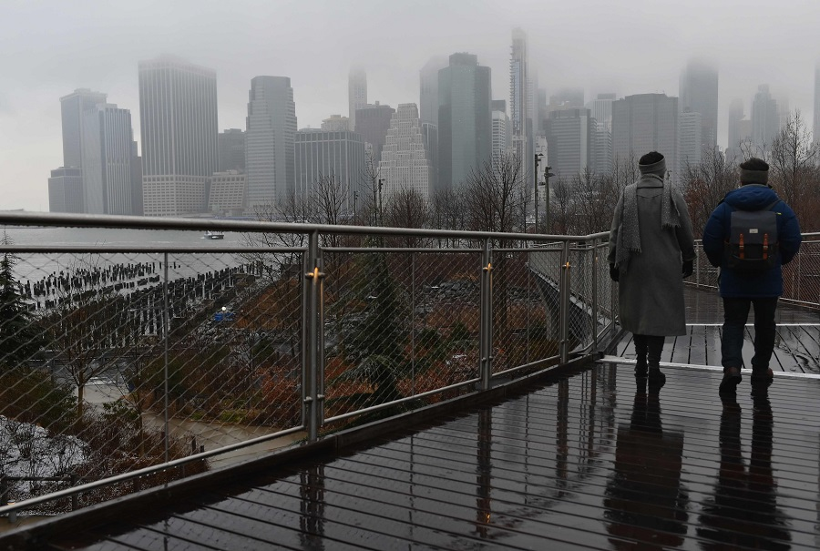 People walk in the Brooklyn borough after a winter storm brought snow and rain on 26 January 2021 in New York City, US. (Angela Weiss/AFP)