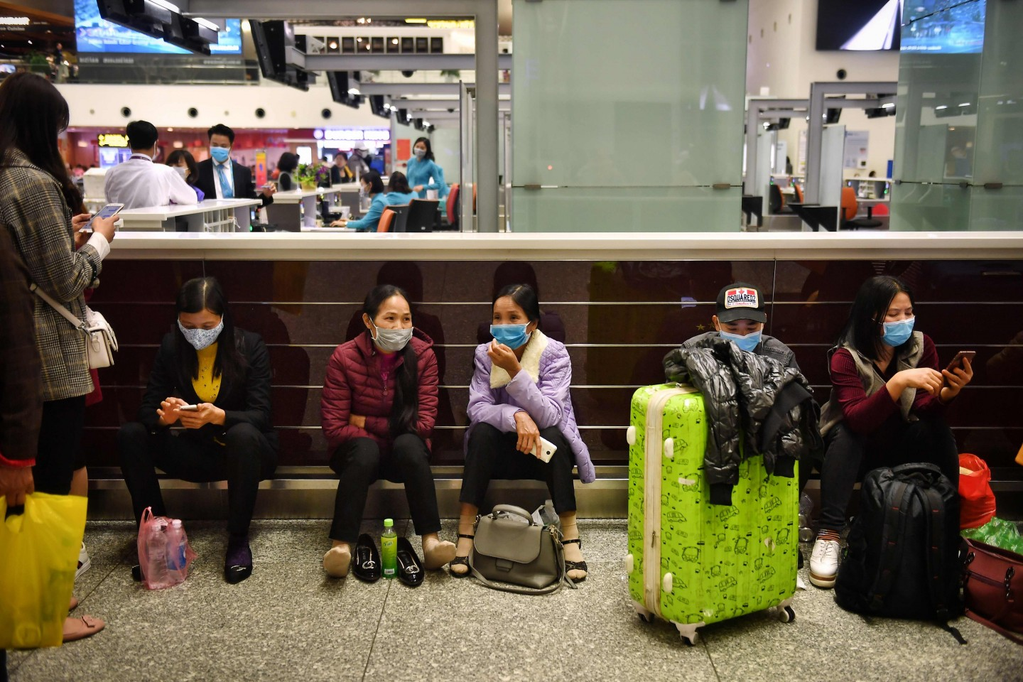 Passengers wear protective facemasks in the departure hall of Noi Bai International Airport in Hanoi on 6 February 2020. Health officials in Vietnam said on 5 February that all foreign passport holders, including those from China, Hong Kong and Macau, that have been to mainland China in the past 14 days will not be permitted to enter Vietnam. (Lillian Suwanrumpha/AFP)