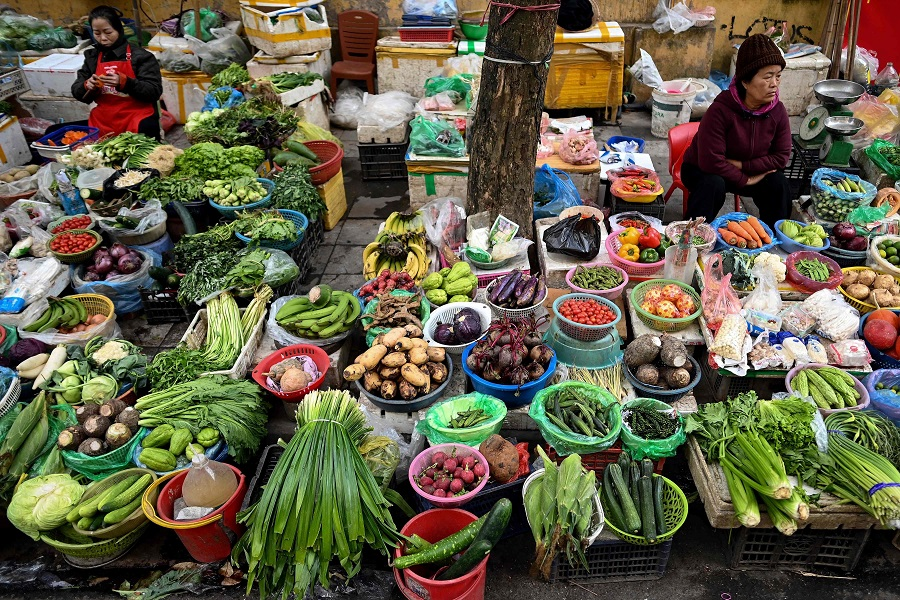 Vegetable vendors wait for customers along a street in Hanoi on 12 January 2021. (Manan Vatsyayana/AFP)