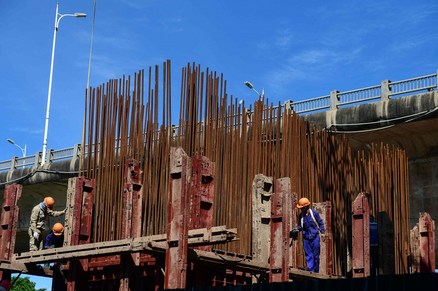 Workers work on a bridge construction project in Hanoi, Vietnam, on 15 June 2021. (Nhac Nguyen/AFP)