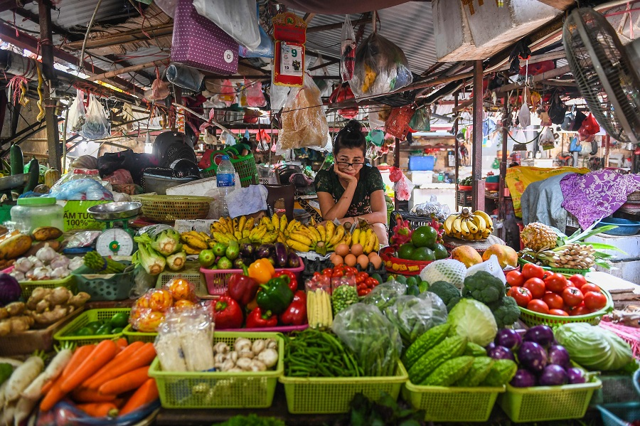 A vegetable vendor waits for customers at a market in Hanoi on 29 September 2020. (Nhac Nguyen/AFP)