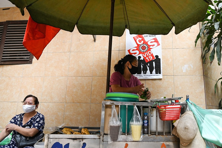 A Vietnamese vendor sells food in the old quarters of Hanoi on 29 April 2020. (Manan Vatsyayana/AFP)