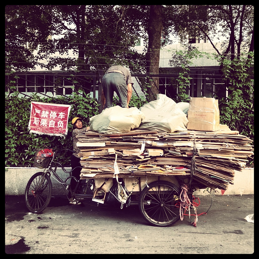 A couple packing their tricycle high with discarded cardboard in Changning, Shanghai. They are an all too familiar scene in many cities in China.