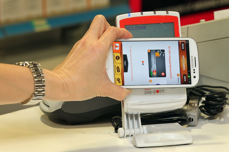 A mobile phone equipped with a near field communication (NFC) capability can be used to pay for purchases, as pictured at a Watsons store in Raffles City Shopping Centre, Singapore. (SPH)