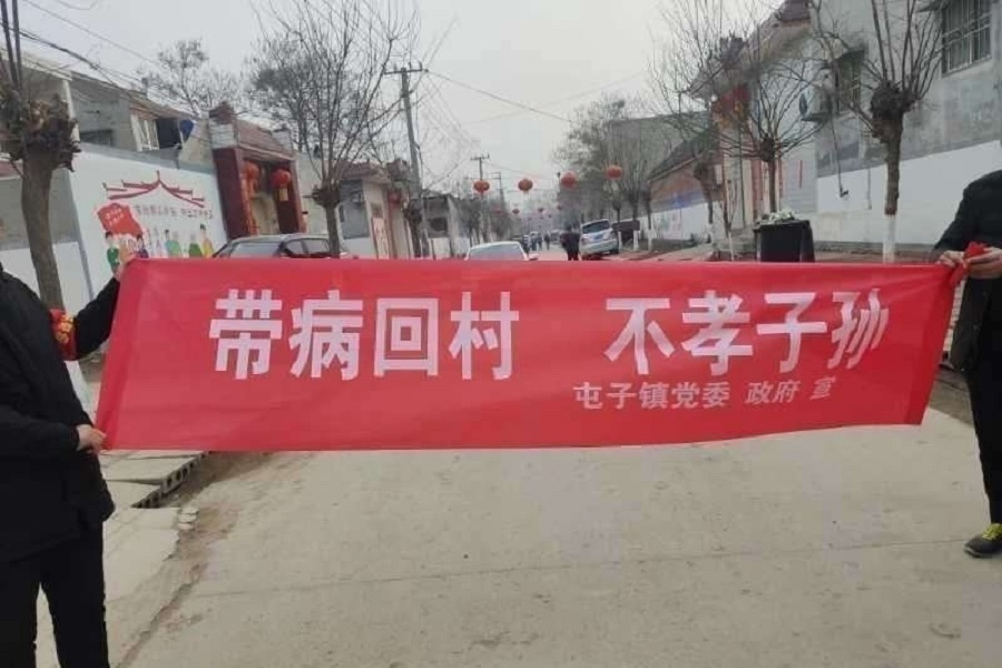 "Another banner held up by villagers reads: ""You people who bring the virus back home are unfilial!"""