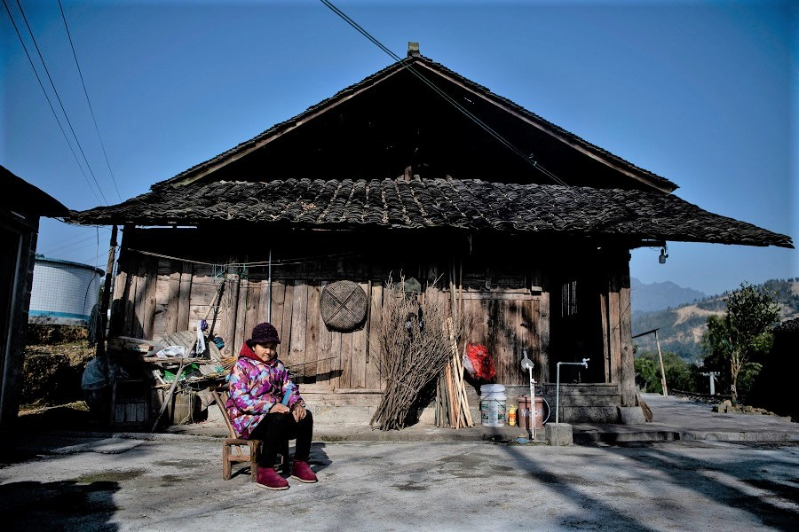 This picture taken on 12 January 2021 shows a woman sitting in front of her residence in Baojing County, Hunan province, China. (Noel Celis/AFP)