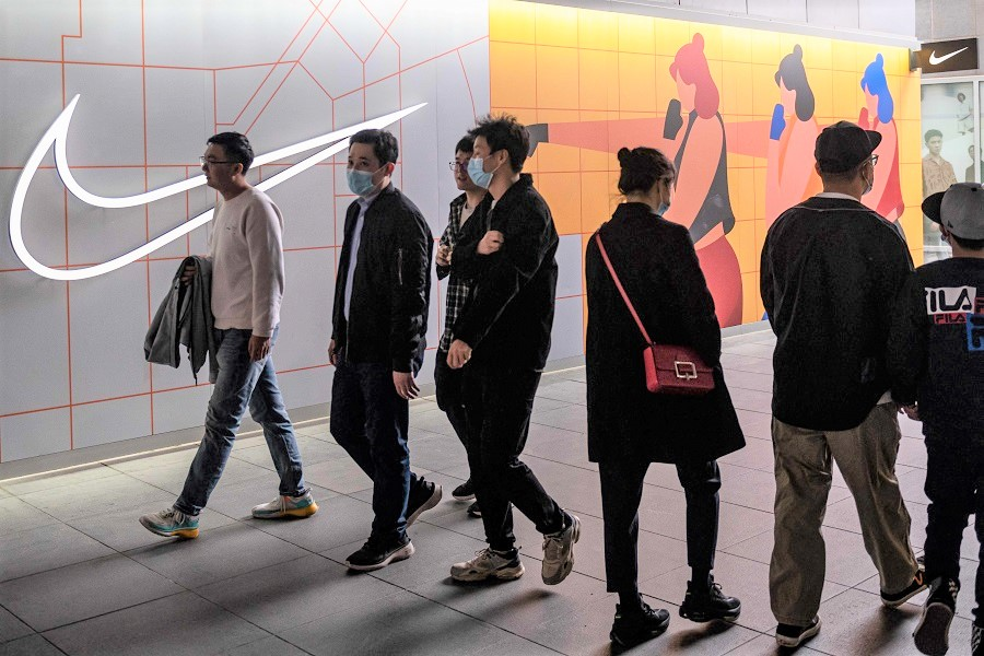 People walk past a Nike store in Beijing, China, on 5 April 2021. (Nicolas Asfouri/AFP)