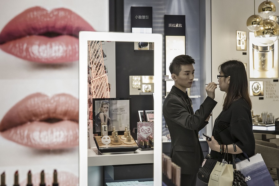 A sales asssitant helps a customer try on a lip color at an Estee Lauder store in the Raffles City shopping mall in Shanghai, China, on 31 May 2017. (Qilai Shen/Bloomberg)
