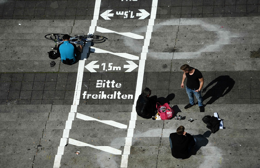 People sit at the stairs of the Burgplatz with painted lines for social distancing at the Rhine promenade in Dusseldorf, Germany, on 12 July 2020. (Ina Fassbender/AFP)