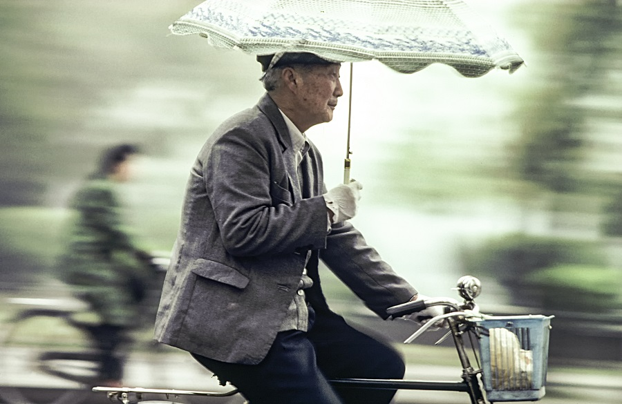 An old man rides his bicycle on a street in Beijing, China, 1982. (iStock)