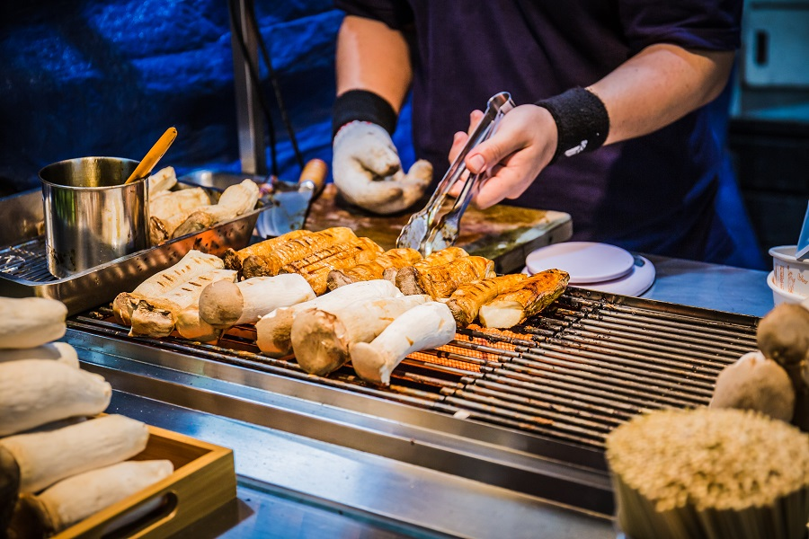 A food stall selling grilled king oyster mushrooms on sticks at the Feng Chia Night Market. (iStock)
