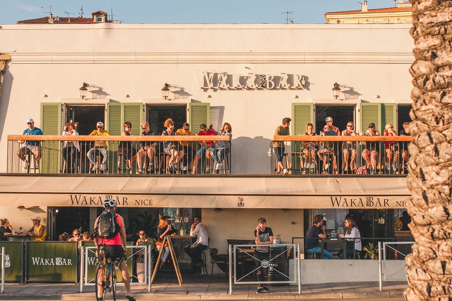 People relax on the balconies of a cafe overlooking the sea. (iStock)