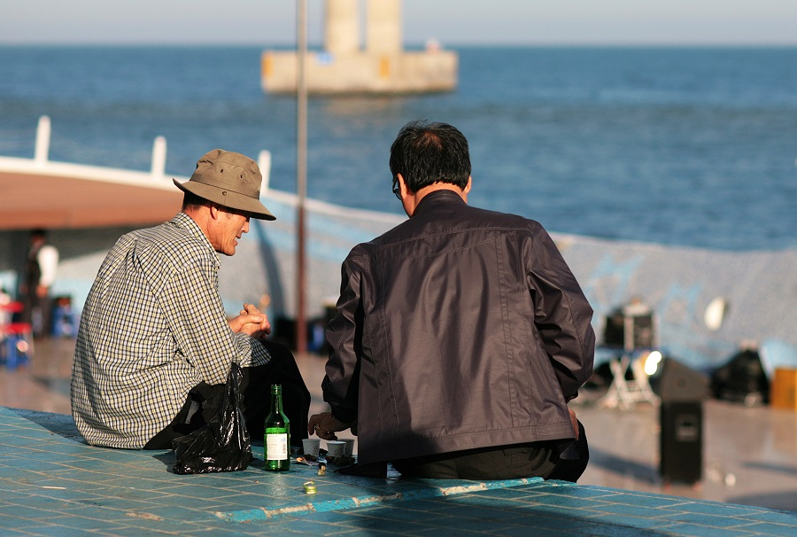 Two men drink soju on the Busan waterfront in South Korea. (iStock)