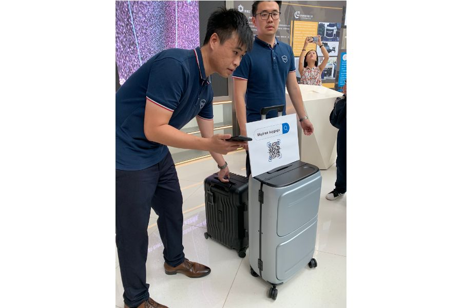 """At the Qianhai """"Dream Factory"""", young Hong Kong entrepreneur Kwok Wai-keung (left) demonstrates the smart luggage that he and his team have developed, equipped with location and self-weighing capabilities. (Photo: Han Yong Hong)"""