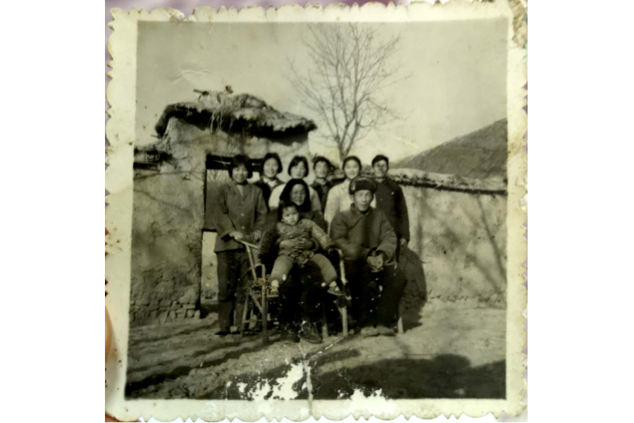Tang Jinglin photographed in 1980 with his parents and siblings before their old residence. After household-based contracting was implemented in their village, the whole family never went hungry again. Life improved significantly, but they were still far from affluent. The family continued living in thatched huts. (Photo: Tang Jinglin)