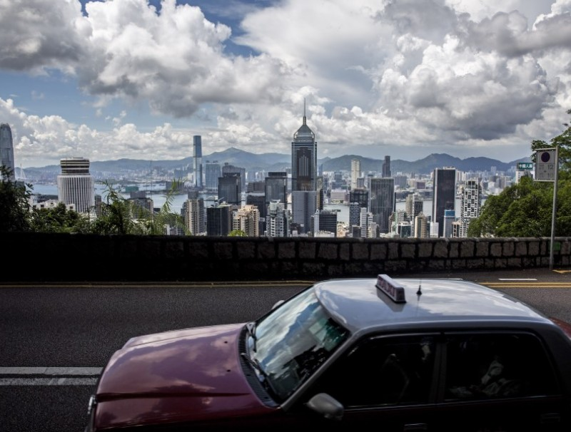 A taxi drives along a road before the city skyline in Hong Kong on 15 August 2020. (Isaac Lawrence/AFP)
