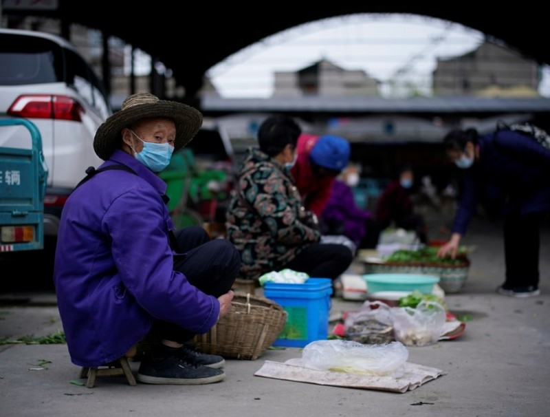 Street vendors wait for customers at their vegetable stalls in Jingzhou, 27 March 2020. (Aly Song/REUTERS)