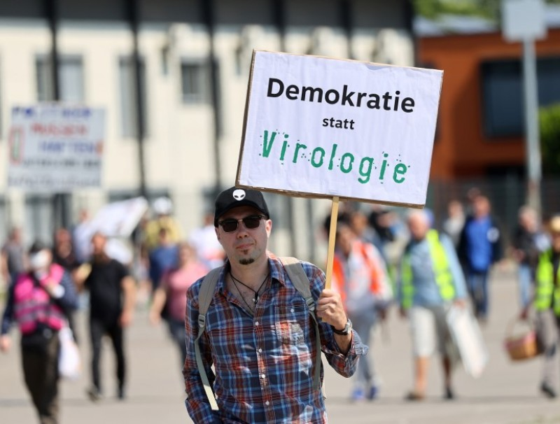 "A man holds up a sign reading ""democracy instead of virology"" as he attends a protest against the government's restrictions following the coronavirus disease (COVID-19) outbreak, at Cannstatter Wasen area in Stuttgart, Germany, May 16, 2020. (Kai Pfaffenbach/REUTERS)"