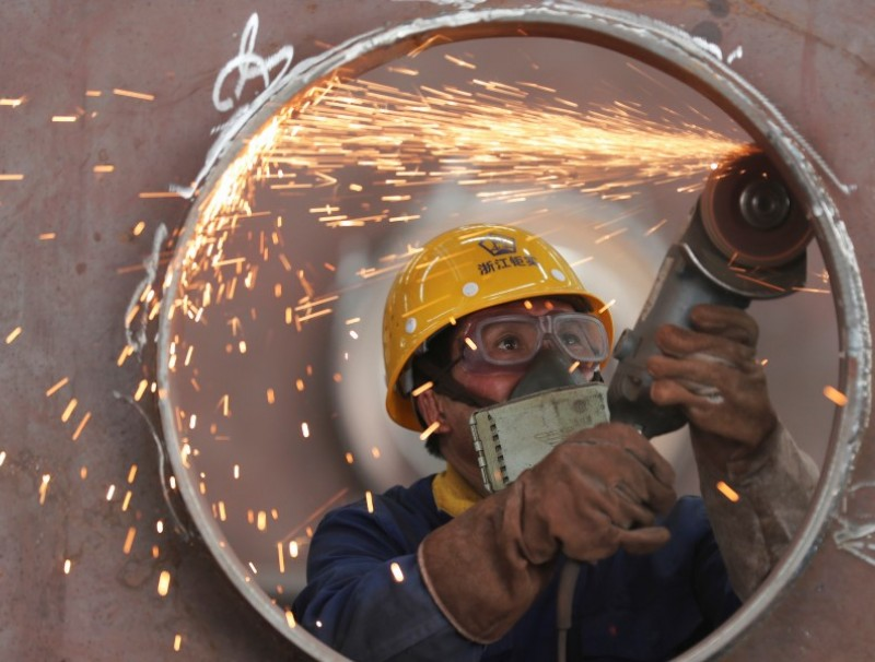 An employee works on a production line manufacturing steel structures at a factory in Huzhou, Zhejiang province, China, on 17 May 2020. (China Daily via Reuters)