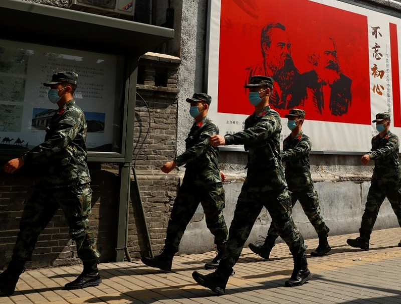 Chinese servicemen walk past portraits of German philosophers Karl Marx and Friedrich Engels and patrol a street near the Great Hall of the People on the opening day of the National People's Congress (NPC) in Beijing, China, on 22 May 2020. (Thomas Peter/Reuters)