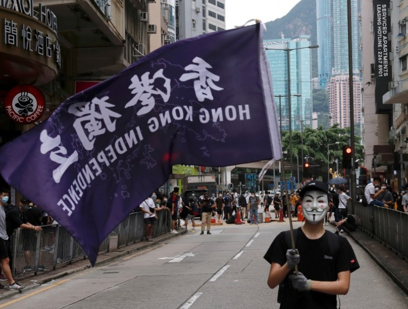 A masked anti-government protester holds a flag supporting Hong Kong independence during a march against Beijing's plans to impose national security legislation in Hong Kong, 24 May 2020. (Tyrone Siu/REUTERS)