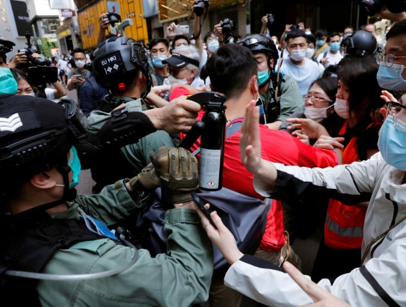 Anti-government demonstrators scuffle with riot police during a lunch time protest as a second reading of a controversial national anthem law takes place in Hong Kong, 27 May 2020. (Tyrone Siu/REUTERS)