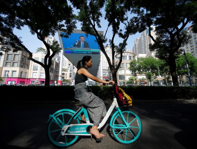 A woman cycles past a screen showing a news conference by Chinese Premier Li Keqiang after the closing session of the National People's Congress, in Beijing, China, on 28 May 2020. (Thomas Peter/Reuters)