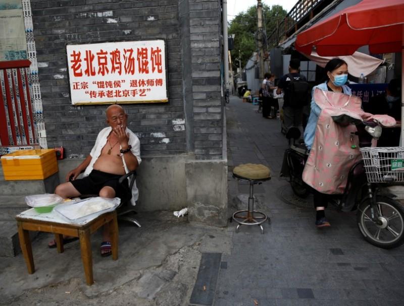 A man smokes at a stall selling frozen wonton near a hutong neighborhood in Beijing, 5 June 2020. (Tingshu Wang/REUTERS)