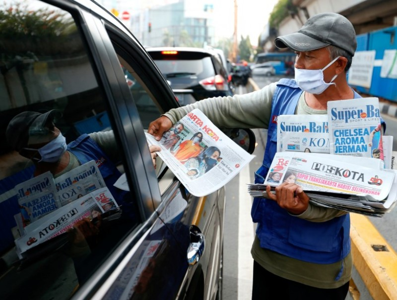 A vendor sells newspapers along a highway in Jakarta, Indonesia, 10 June 2020. (Ajeng Dinar Ulfiana/REUTERS)