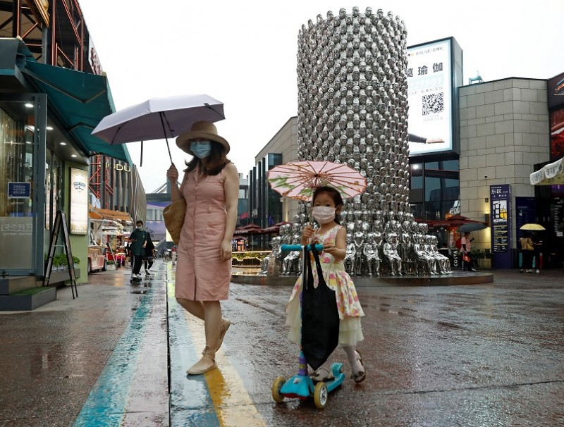 People wear protective face masks at a shopping complex in Beijing, China, on 17 July 2020. (Thomas Peter/Reuters)