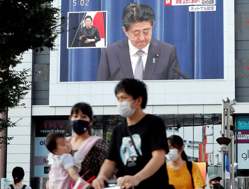 People wearing protective face masks walk past a large screen broadcasting a news conference of Japan Prime Minister Shinzo Abe in Tokyo, Japan, 28 August 2020. (Kim Kyung-Hoon/Reuters)