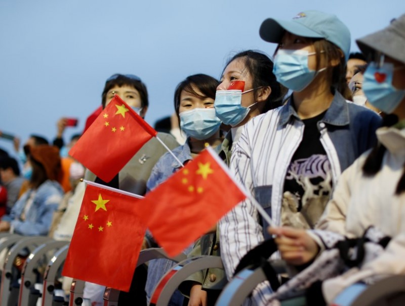 People wearing face masks, following the coronavirus disease (Covid-19) outbreak, hold China flags attend a flag-raising ceremony at Tiananmen Square on National Day to mark the 71st anniversary of the founding of People's Republic of China, in Beijing, China, 1 October 1, 2020. (Carlos Garcia Rawlins/REUTERS)