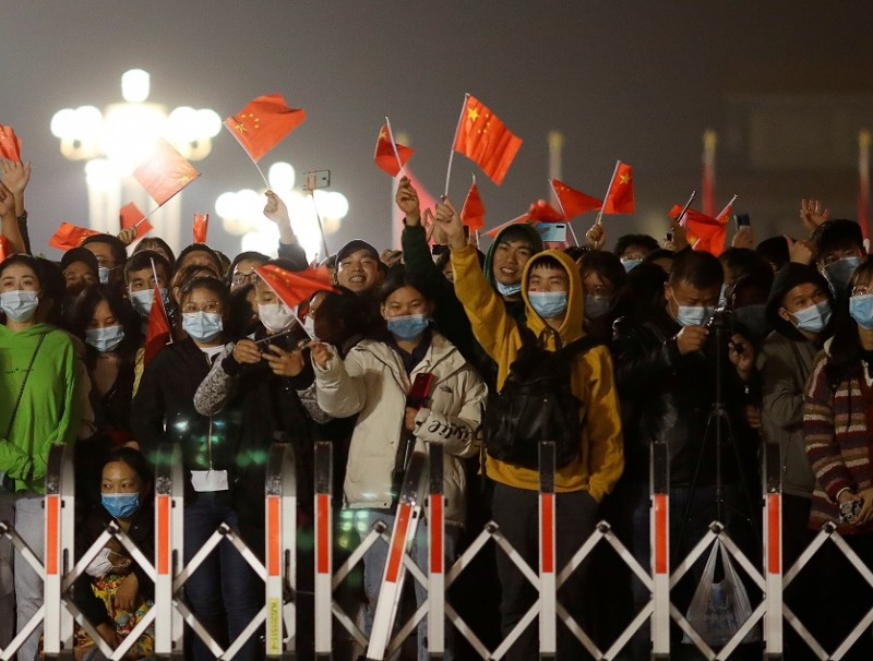People wearing face masks wave China flags during a flag-raising ceremony at Tiananmen Square on National Day to mark the 71st anniversary of the founding of People's Republic of China, in Beijing, China, 1 October 2020. (Carlos Garcia Rawlins/Reuters)