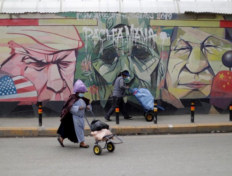 Women walk past a graffiti depicting US President Donald Trump, the Pachamama (Mother Earth) and Chinese President Xi Jinping, in El Alto, Bolivia, 16 October 2020. (Ueslei Marcelino/Reuters)