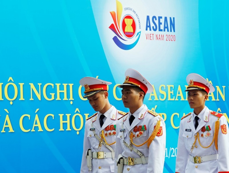 Military personnel walk past a banner promoting the ASEAN summit in Hanoi, Vietnam, 11 November 2020. (Kham/Reuters)