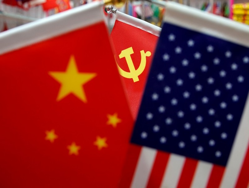 The flags of China, the United States and Chinese Communist Party are displayed in a flag stall at the Yiwu Wholesale Market in Yiwu, Zhejiang province, China, 10 May 2019. (Aly Song/File Photo/Reuters)