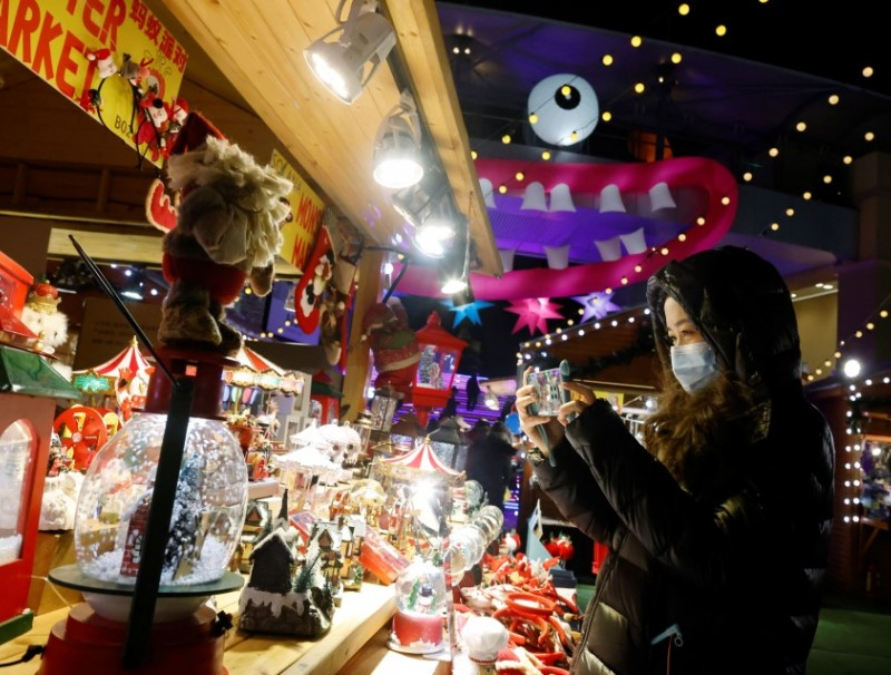 A woman wearing a face mask takes a picture of a display at a Christmas market in a shopping mall following an outbreak of the coronavirus disease (COVID-19) in Beijing, 16 December 2020. (Thomas Peter/Reuters)