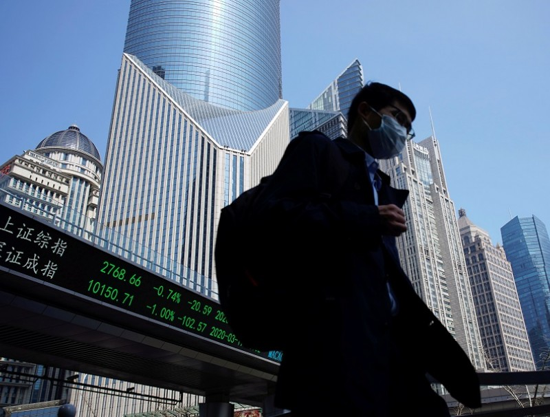 A pedestrian wearing a face mask walks near an overpass with an electronic board showing stock information, at Lujiazui financial district in Shanghai, China, 17 March 2020. (Aly Song/File Photo/Reuters)